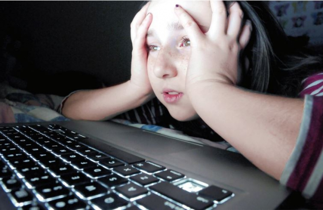 A young person in front of a computer.