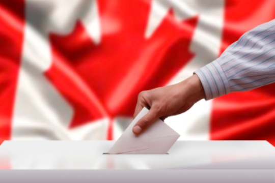 Voting in Canada, a hand puts a ballot in a box.