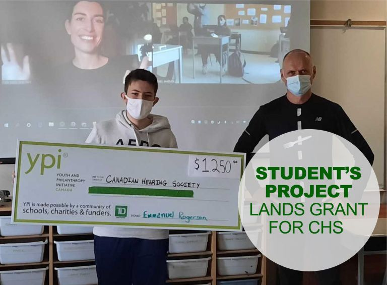 Student and teacher stand holding oversized cheque