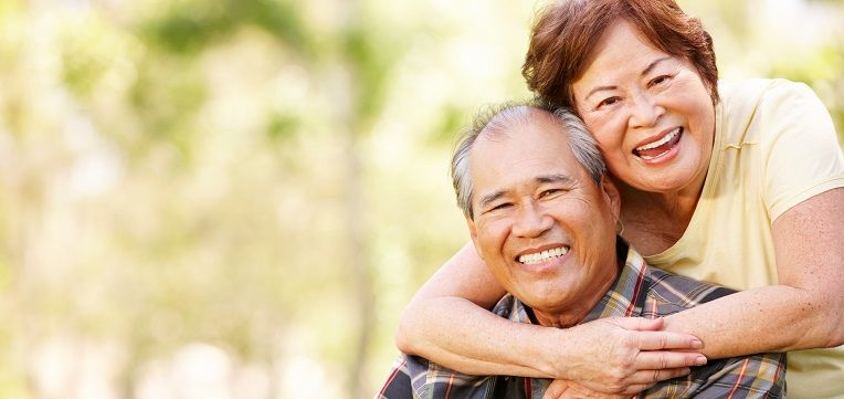 older asian couple hugging and smiling